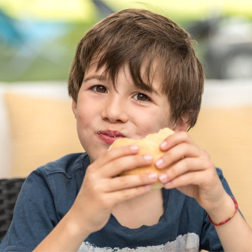child-eating-a-hamburger-picture-id1148216248