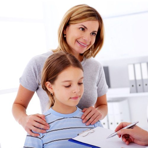 happy-mother-and-daughter-during-visit-at-the-doctors-office-picture-id109722992