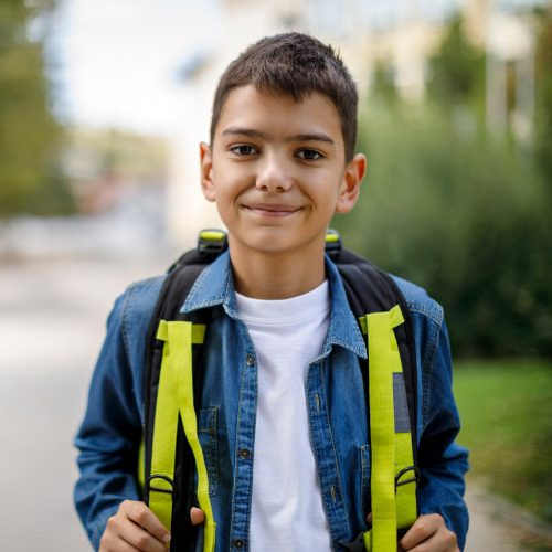 smiling-teenage-boy-with-school-bag-in-front-of-school-picture-id1175573811