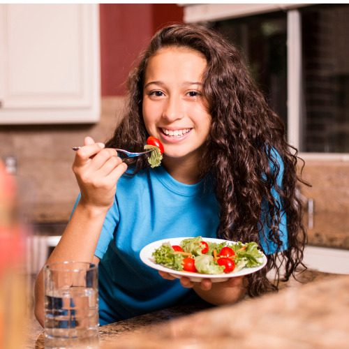teenage-girl-eating-salad-for-dinner-after-school-picture-id610546280